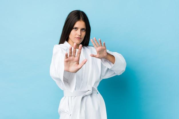 Jeune femme caucasienne pratiquant le karaté isolé sur un mur bleu