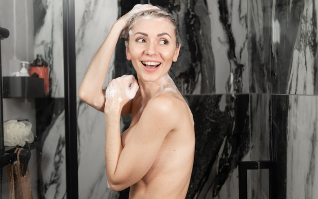 Jeune femme caucasienne prend une douche. cheveux sur ma tête avec de la mousse de shampoing, j'ai vu quelqu'un et sourire joyeusement. vue latérale, bannière