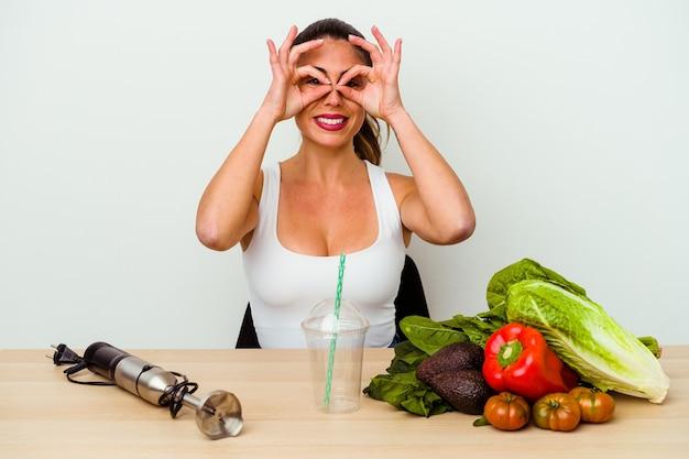 Jeune femme caucasienne préparant un smoothie sain avec des légumes montrant un signe correct sur les yeux