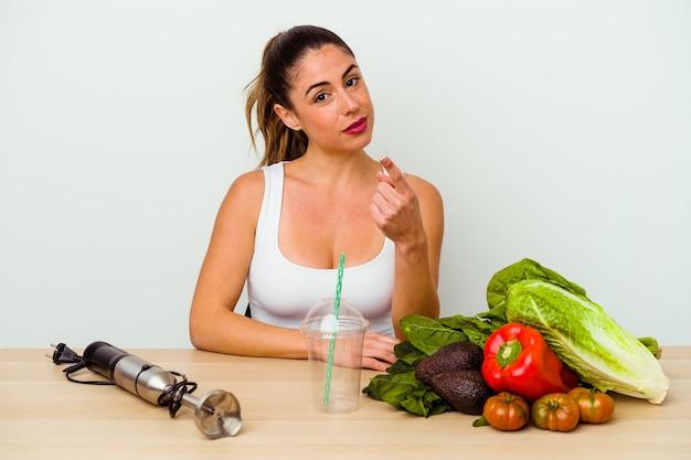 Jeune femme caucasienne préparant un smoothie sain avec des légumes pointant du doigt vers vous comme si vous vous invitiez à vous rapprocher.
