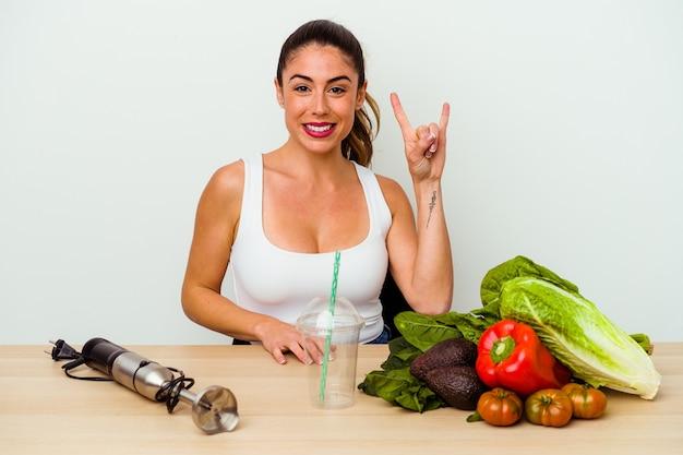 Jeune femme caucasienne prépare un smoothie sain avec des légumes montrant un geste de cornes comme un concept de révolution.