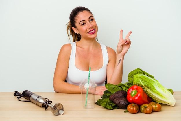Jeune femme caucasienne, préparer un smoothie sain avec des légumes joyeux et insouciant montrant un symbole de paix avec les doigts.