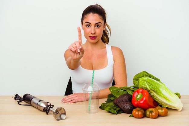 Jeune femme caucasienne, préparer un smoothie sain avec des légumes montrant le numéro un avec le doigt.