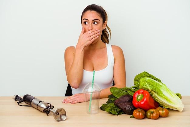 Jeune femme caucasienne, préparer un smoothie sain avec des légumes réfléchis à la recherche d'un espace de copie couvrant la bouche avec la main.