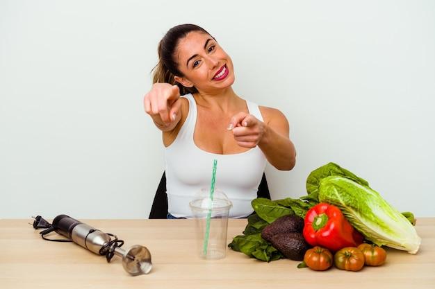 Jeune femme caucasienne, préparer un smoothie sain avec des légumes sourires joyeux pointant vers l'avant.