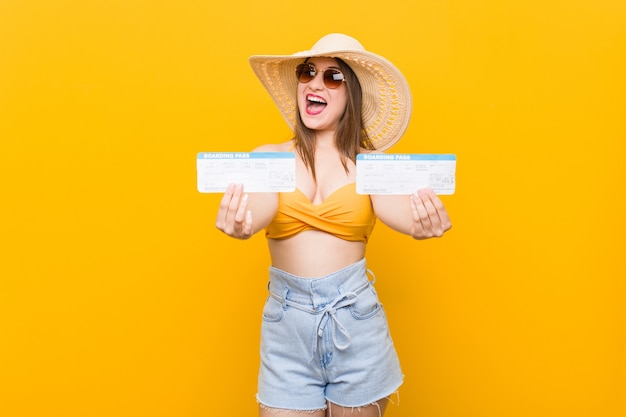 Jeune femme caucasienne prête à aller à la plage avec un billet d'avion
