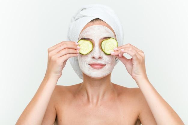 Jeune femme caucasienne, profitant d'un traitement de masque offacial avec du concombre