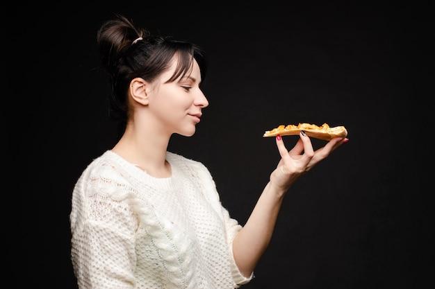 Jeune femme caucasienne avec queue manger un morceau de pizza.