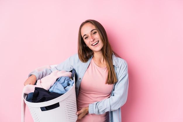 Jeune femme caucasienne ramasser des vêtements sales isolés rire et s'amuser.