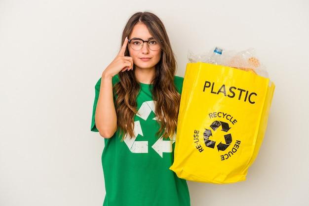 Jeune femme caucasienne recyclant un plein de plastique isolé sur fond blanc pointant le temple avec le doigt, pensant, concentré sur une tâche.