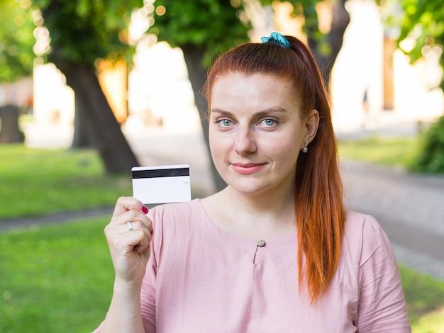 Jeune femme caucasienne reste dans le parc et montre une carte de crédit blanche avec une ligne magnétique noire.