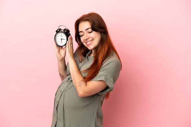 Jeune femme caucasienne rousse isolée sur fond rose enceinte et tenant l'horloge