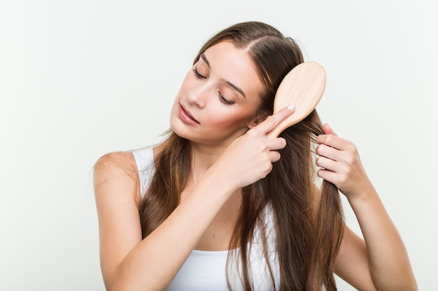Jeune femme caucasienne se brosser les cheveux