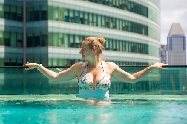 Jeune femme caucasienne se détendre dans une piscine sur le toit d'un gratte-ciel dans une métropole sous le soleil....