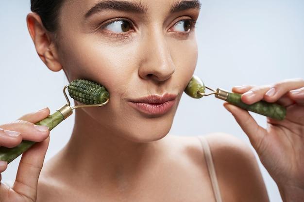 Jeune femme caucasienne sérieuse massant sa peau du visage
