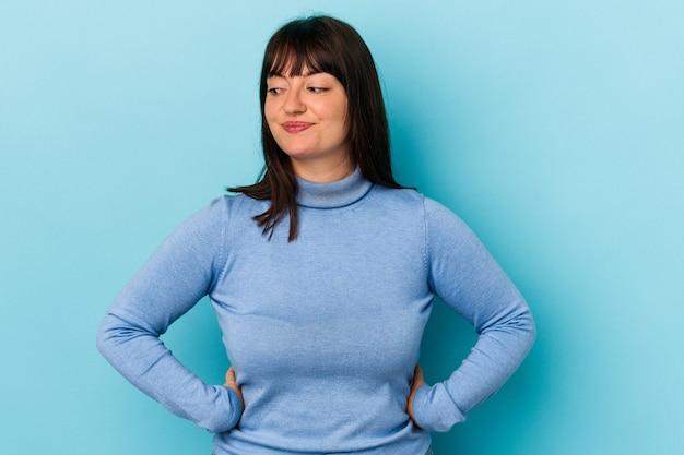 Jeune femme caucasienne sinueuse isolée sur fond bleu rit joyeusement et s'amuse à garder les mains sur le ventre.