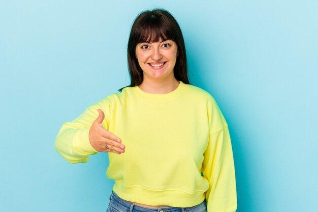 Jeune femme caucasienne sinueuse isolée sur fond bleu s'étendant la main à la caméra en geste de salutation.