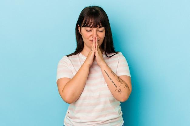 Jeune femme caucasienne sinueuse isolée sur fond bleu, tenant la main dans la prière près de la bouche, se sent confiante.