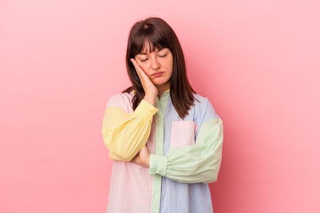 Jeune femme caucasienne sinueuse isolée sur fond rose qui s'ennuie, est fatiguée et a besoin d'une journée de détente.