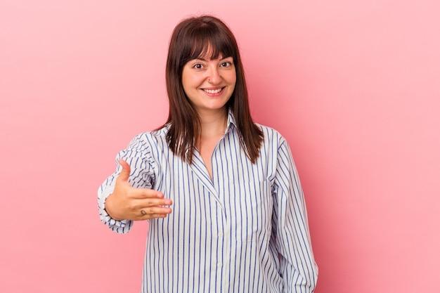 Jeune femme caucasienne sinueuse isolée sur fond rose s'étendant la main à la caméra en geste de salutation.