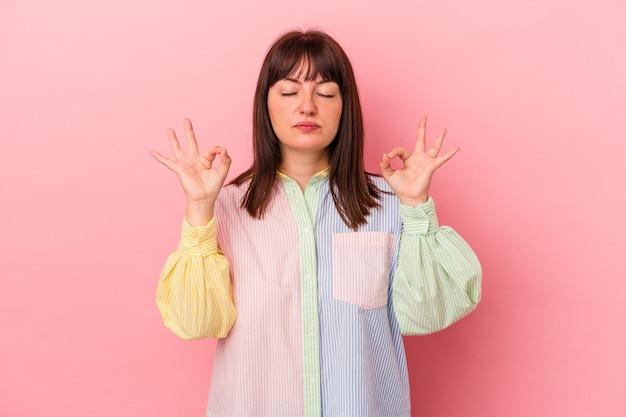 Jeune femme caucasienne sinueuse isolée sur fond rose se détend après une dure journée de travail, elle fait du yoga.