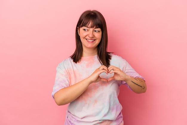Jeune femme caucasienne sinueuse isolée sur fond rose souriante et montrant une forme de coeur avec les mains.