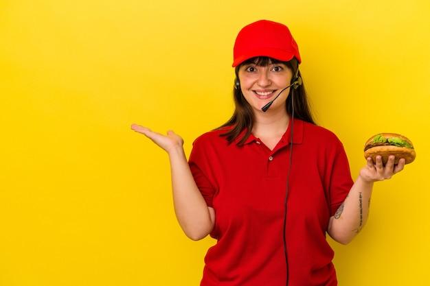 Jeune femme caucasienne sinueuse tenant un hamburger isolé sur fond jaune montrant un espace de copie sur une paume et tenant une autre main sur la taille.