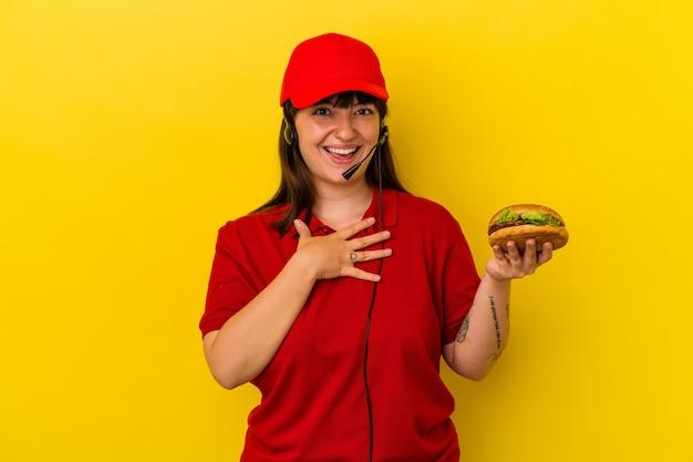Jeune femme caucasienne sinueuse tenant un hamburger isolé sur fond jaune rit fort en gardant la main sur la poitrine.