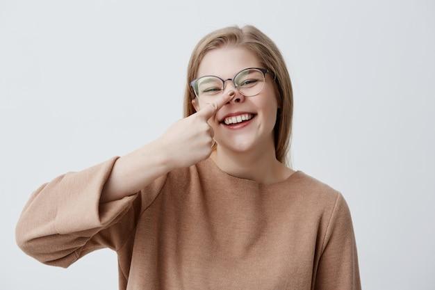La jeune femme caucasienne sombre se moque, touche son nez, se moque, rit et sourit largement, montre ses dents blanches et uniformes. fille blonde positive sourit joyeusement