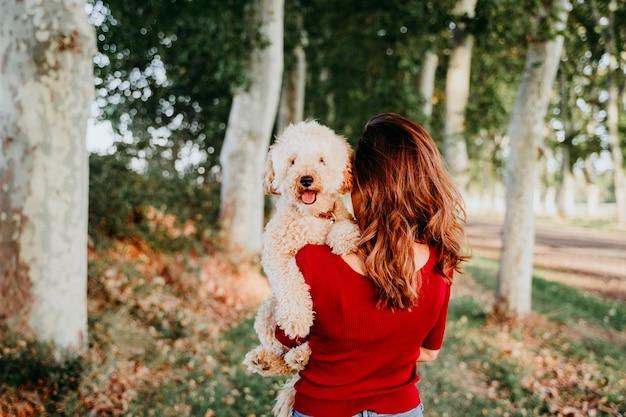 Jeune femme caucasienne avec son chien caniche dans une voiture