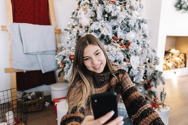 Jeune femme caucasienne souhaite joyeux noël par appel vidéo à l'aide de téléphone mobile en vacances à la maison sur le canapé.