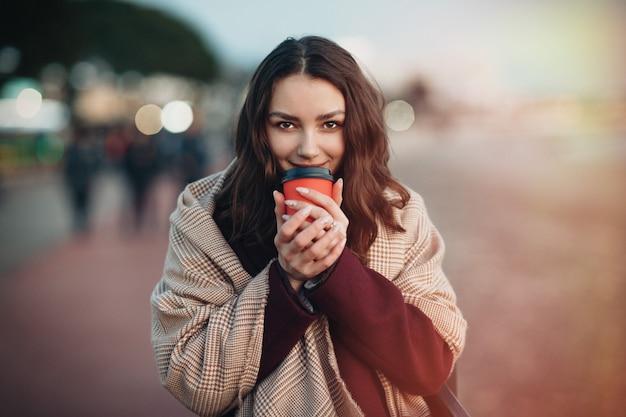 Jeune femme caucasienne souriante, boire une boisson chaude de la tasse à emporter.