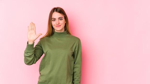 Jeune femme caucasienne souriante joyeuse montrant le numéro cinq avec les doigts.