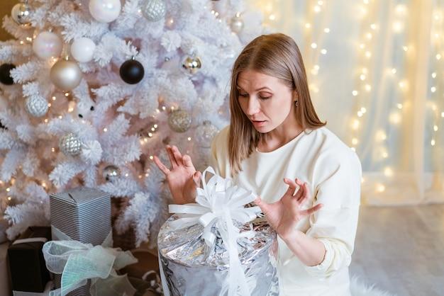 Une jeune femme caucasienne souriante ouvre une boîte avec un cadeau de noël, un mode de vie de noël et un centre commercial ...