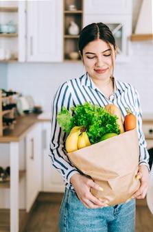 Jeune femme caucasienne souriante tenir le sac à provisions écologique avec des légumes frais et de la baguette dans une cuisine moderne.