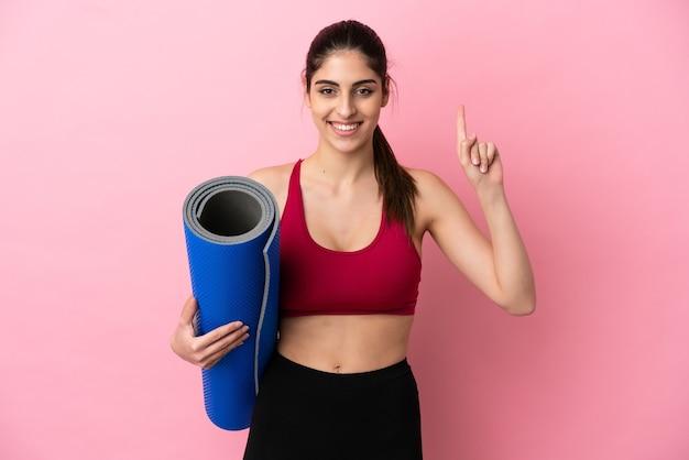 Jeune femme caucasienne sportive allant à des cours de yoga tout en tenant un tapis pointant vers une excellente idée