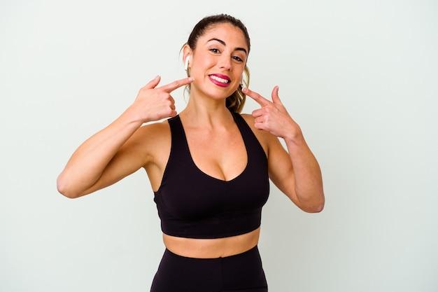 Jeune femme caucasienne sportive isolée sur des sourires blancs, pointant du doigt la bouche.