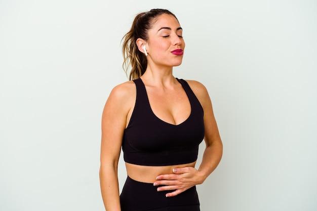 Jeune femme caucasienne sportive isolée sur le ventre blanc touche le ventre, sourit doucement, mange et satisfait le concept.