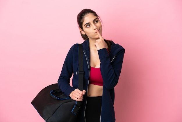 Jeune femme caucasienne sportive avec sac de sport isolé sur fond rose ayant des doutes en levant les yeux