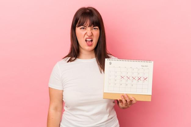 Jeune femme caucasienne en surpoids tenant un calendrier isolé sur fond rose criant très en colère et agressive.