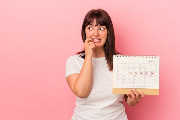Jeune femme caucasienne en surpoids tenant un calendrier isolé sur fond rose détendue en pensant à quelque chose en regardant un espace de copie.