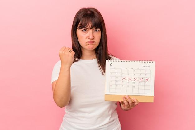 Jeune femme caucasienne en surpoids tenant un calendrier isolé sur fond rose montrant le poing à la caméra, expression faciale agressive.