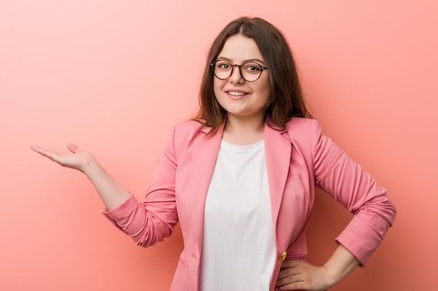 Jeune femme caucasienne de taille plus entreprise montrant un espace de copie sur une paume et tenant une autre main sur la taille.