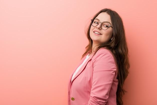Jeune femme caucasienne de taille plus entreprise regarde de côté souriant, gai et agréable.