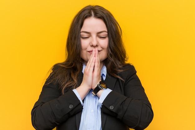 Jeune femme caucasienne de taille plus, tenant les mains en prière près de la bouche, se sent confiant.