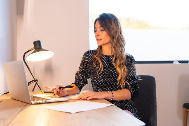 Jeune femme caucasienne télétravaillant avec un ordinateur et un bloc-notes