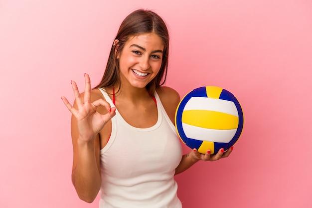 Jeune femme caucasienne tenant un ballon de volley-ball isolé sur fond rose joyeux et confiant montrant un geste ok.