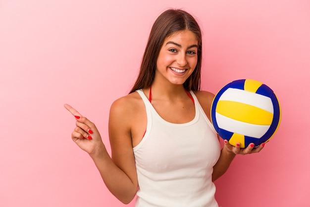 Jeune femme caucasienne tenant un ballon de volley isolé sur fond rose souriant et pointant de côté, montrant quelque chose dans un espace vide.