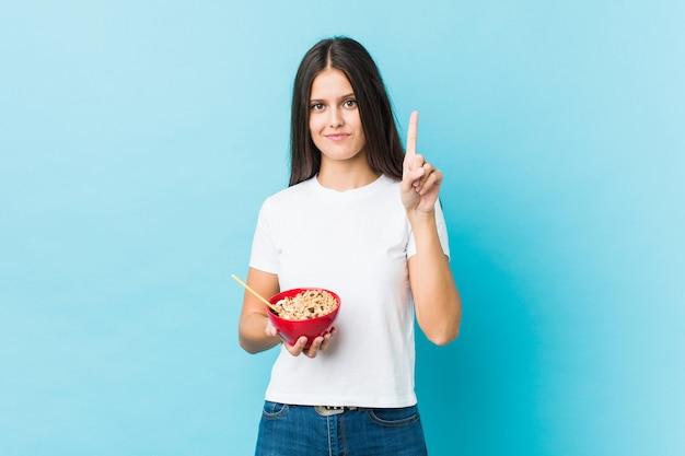 Jeune femme caucasienne tenant un bol de céréales montrant le numéro un avec le doigt.