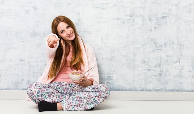 Jeune femme caucasienne tenant un bol de céréales sourires joyeux pointant vers l'avant.